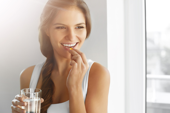 Smiling Woman Taking Weight Loss Pill